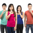 Group of Chinese friends with fingers over lips. — Stock Photo