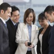 Foto Stock: Group of business people looking at smartphone
