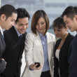 A group of business people looking at a smartphone — Stok fotoğraf