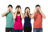 Four Chinese people with their hands over their eyes. — Stock Photo