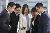 A group of business people looking at a smartphone — Stock Photo