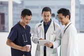 Team of male doctors using a digital tablet — Stockfoto