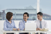 Asian business colleagues working around a laptop — Stock Photo