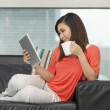 Asian woman at home reading a tablet PC. — Stock Photo #36805111