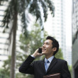 Chinese business man using a smartphone. — Stock Photo