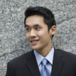 Happy young Chinese business man in modern city — Stock Photo #36809119