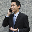 Chinese Business man sending a text. — Stock Photo