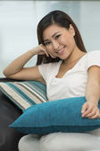 Young Asian woman at home on sofa relaxing. — Stock Photo