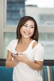Mujer asiática en casa utilizando un teléfono — Foto de Stock