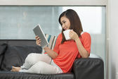 Asian woman at home reading a tablet PC. — Foto de Stock