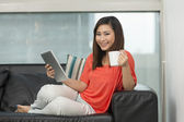Asian woman at home reading a tablet PC. — Stock Photo