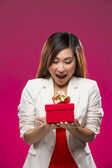 Happy Chinese woman holding a christmas gift. — Stock Photo