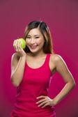 Happy Chinese Woman holding an apple on pink background. — Stock Photo
