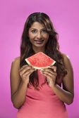 Happy Indian Woman eating watermelon on pink background — Stock Photo