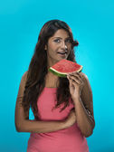 Happy Indian Woman eating watermelon on blue background — Stock Photo