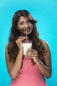 Indian Woman drinking glass of milk on blue background. — Stock Photo