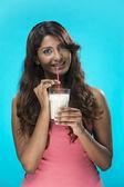 Donna indiana a bere il bicchiere di latte su sfondo blu. — Foto Stock