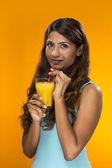 Indische frau trinkt orangensaft auf farbigen hintergrund — Stockfoto