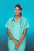 Female Indian doctor an blue background. — Stock Photo