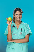 Indian doctor holding an apple. — Stock Photo