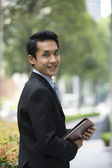 Happy young Chinese business man in modern city — Stock Photo
