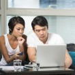 Young Chinese couple using a laptop at home — Stock Photo