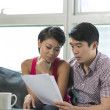 Serious Asian couple reading a financial bill — Stock Photo