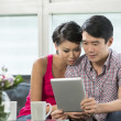 Young Chinese couple using a digital tablet — Stock Photo #36810611
