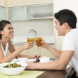 Happy Asian couple eating at home — 图库照片