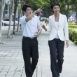 Two of Asian business colleagues walking in street — Stock Photo