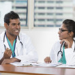 Two Indian doctors sitting working at a desk together — Stock Photo