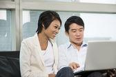Jovem casal chinês usando um laptop em casa — Foto Stock