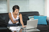 Asian woman on her sofa with a laptop — Stock Photo