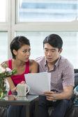 Serious Asian couple reading a financial bill — Stock Photo