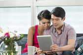 Young Chinese couple using a digital tablet — Stock Photo