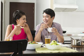 Happy Asian couple eating at home — Stock Photo