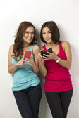 Two happy Asian women using there smartphones. — Stock Photo