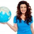 Pretty smiling girl holding globe in right hand — Stock Photo