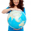 Stock Photo: Cheerful girl holding globe safely with both hands