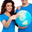Woman pointing at China on globe while man holds it — Stock Photo