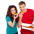 Adorable young couple relishing yummy pizza - Stock Photo