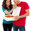 Stock Photo: Caring girlfriend making her boyfriend eat pizza