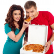 Pretty woman making her boyfriend end pizza piece - Stock Photo