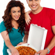Stock Photo: Cheerful love couple enjoying pizztogether