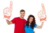 Young couple showing boo hurray foam hand — Stock Photo