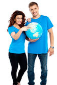 Couple posing for a picture with globe in hand — Stock Photo