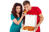 Pretty woman making her boyfriend end pizza piece — Stock Photo