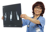Doctor holding x-ray report. Analyzing it — Stock Photo