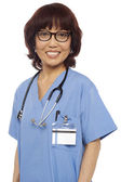 Pleasing female gynecologist posing with stethoscope — Stock Photo