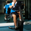 Smart guy working out in the exercise bike — Stock Photo